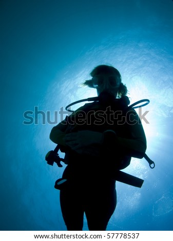 Silhouette of a female diver in the Caribbean Sea - stock photo