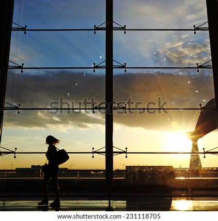 Silhouette of a female traveler against a sunset in an airport lounge with a wide observation window.