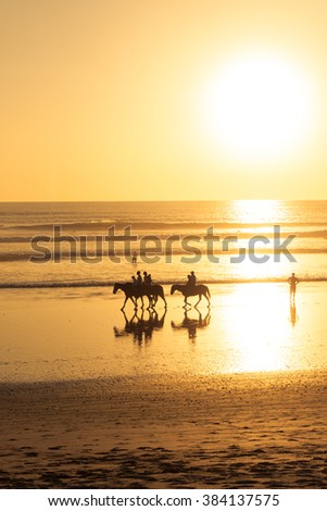 Silhouette of a few horse riders on  beach in Nicaragua - stock photo