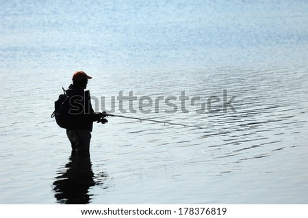 Silhouette of a fisherman  - stock photo