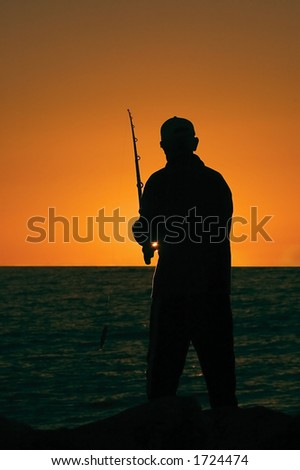 Silhouette of a fisherman as the sun sets on cottesloe beach , Perth - stock photo