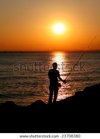 Silhouette of a fisherman by sunset - stock photo