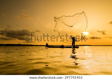 Silhouette of a fisherman throwing his net with sunset. - stock photo
