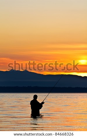 Silhouette of a fisherman with a fishing pole at sunset. - stock photo