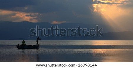 silhouette of a fishermans at sunset - stock photo