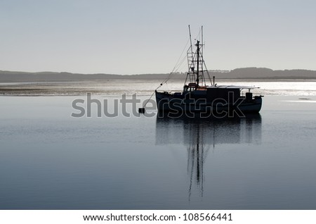 Silhouette of a fishing boat mooring in Northland, New Zealand. - stock photo