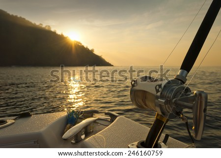 Silhouette of a fishing reel and rod on the boat with sunset - stock photo