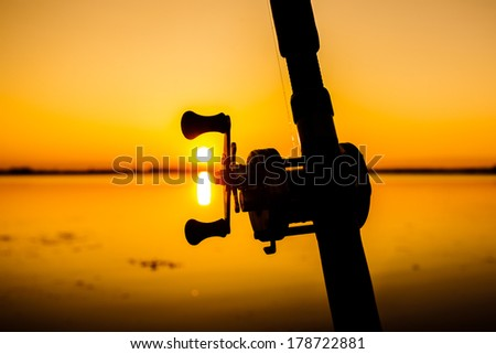 Silhouette of a fishing rod with evening light. - stock photo