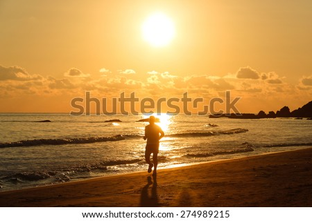 Silhouette of a fit runner at sunset on a sandy beach, enjoying the evening chill of late summer. Active lifestyle, vacation recreation, outdoor activity concept. 