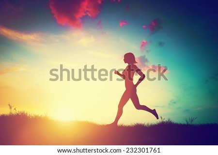 Silhouette of a fit woman running at sunset. Training, jogging, healthy lifestyle. - stock photo
