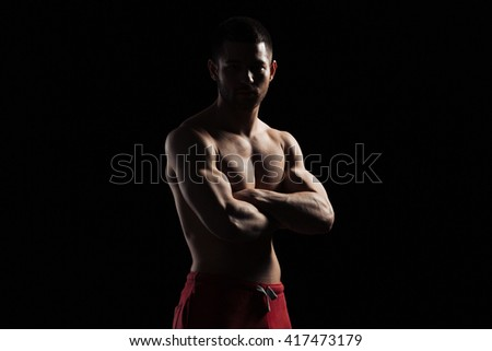 Silhouette of a fitness man standing with arms folded over dark background