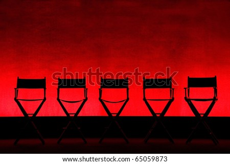 Silhouette of a five traditional wood and canvas Director's Chairs on a red stage background - horizontal