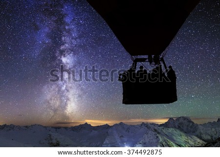 Silhouette of a flying hot air balloon on the background of of the starry sky. - stock photo