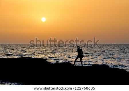 Silhouette of a girl by the water at sunset. - stock photo