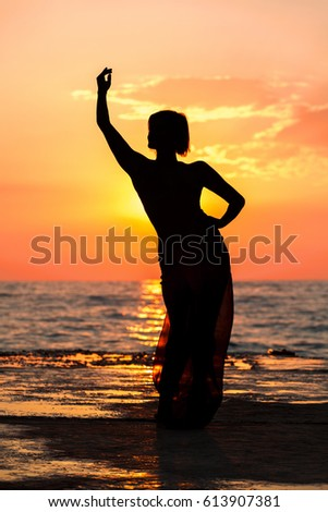 Silhouette of a girl dancing on the background of sea sunset