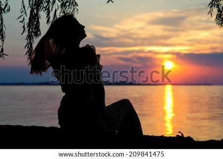 silhouette of a girl in a dress on the beach at sunset - stock photo