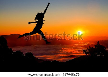 Silhouette of a girl  in front of the sunset on the hill.