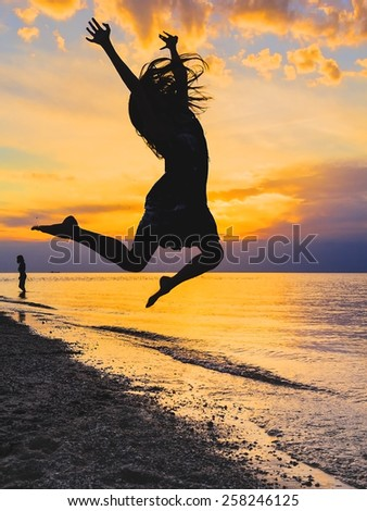 Silhouette of a girl jumping in the sea at sunset - stock photo
