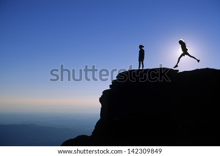 Silhouette of a girl jumping over a rock cliff on top of Mt. Mansfield in Stowe, Vermont