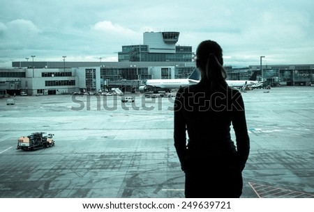 Silhouette of a girl looking at the airport landing ground and control tower - stock photo