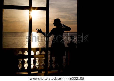 silhouette of a girl near the window on the background sunset in the sea - stock photo