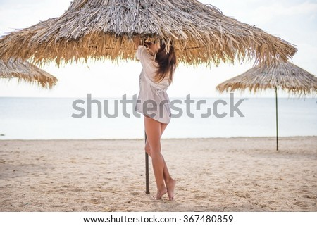 silhouette of a girl on the beach under an umbrella. umbrella of reeds - stock photo