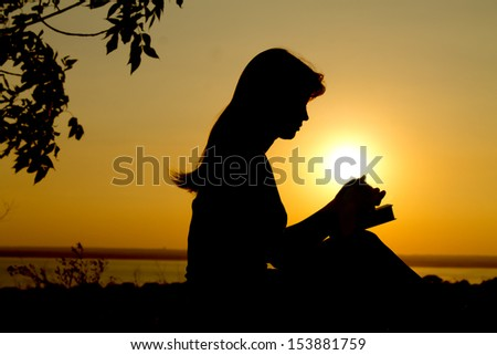 silhouette of a girl praying with the Bible - stock photo