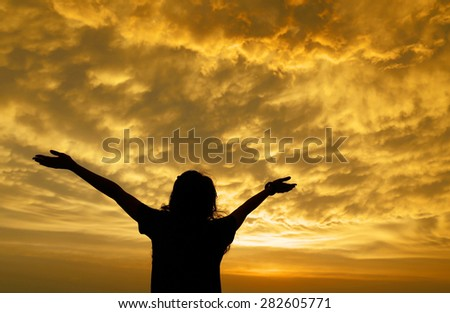 Silhouette of a girl spreading hand toward the clouds in the evenin