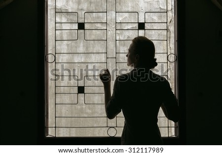 Silhouette of a girl standing in front of an open window, the wall behind him.