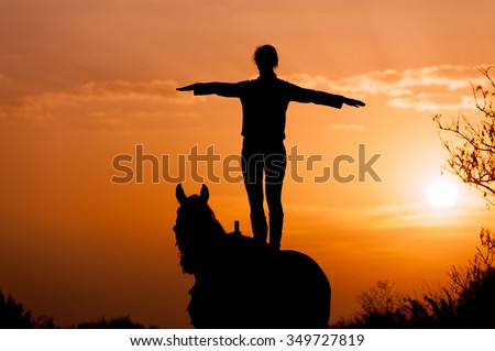 silhouette of a girl standing on a horse on a background of sunset and sunrise. The rider performs a trick. The man straightened his arms like wings - stock photo