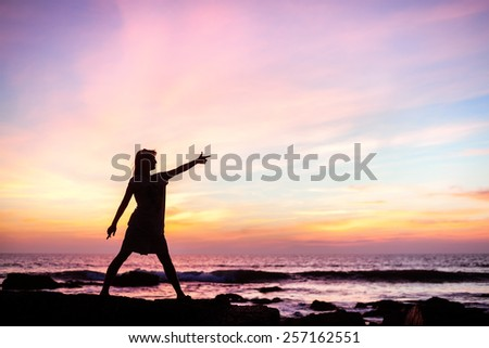 Silhouette of a girl standing on a rock at sunset - stock photo