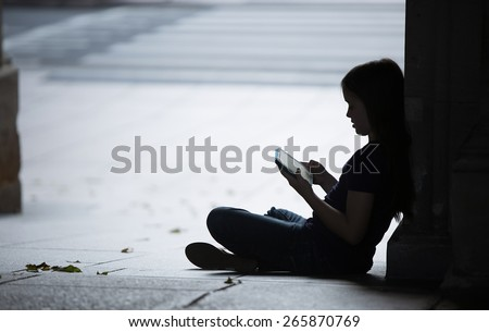 Silhouette of a girl using her tablet computer.  There may  be a predator trying to get to her.