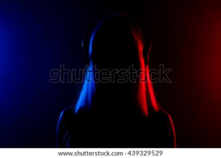 silhouette of a girl with headphones, red and blue lights in the background
