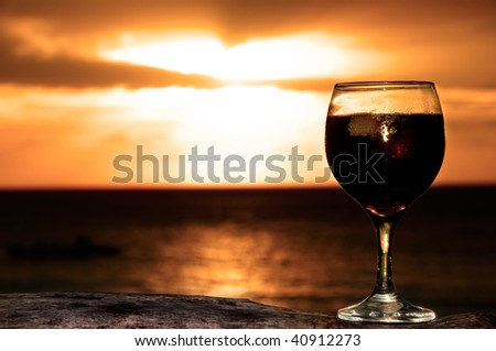 Silhouette of a Glass of wine on the see shore in a lovely evening - stock photo