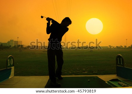 silhouette of a golfer on a bright sky - stock photo