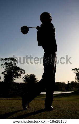 Silhouette of a golfer on the tee box with driver - stock photo