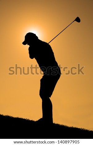 Silhouette of a golfer with a driver about to take a shot with an orange sky. - stock photo
