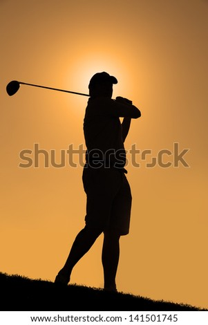 Silhouette of a golfer with a driver having taken a shot with an orange sky. - stock photo
