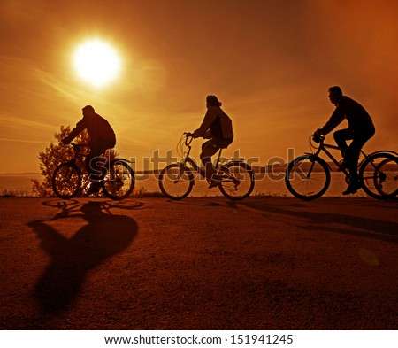 silhouette of a group - 4 four cyclist at orange or yellow sunset With shadow Copy space for inscription - stock photo