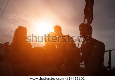 silhouette of a group of friends on a boat - stock photo