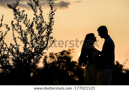 Silhouette of a guy and a girl kissing on sunset background. - stock photo