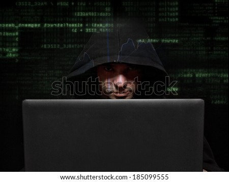 Silhouette of a hacker looking in camera  - stock photo