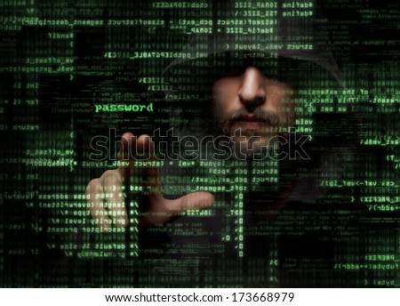Silhouette of a hacker looking in monitor with binary codes and words  - stock photo