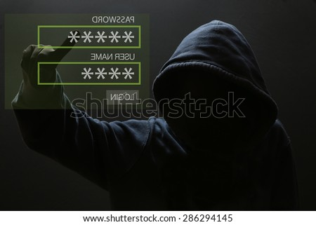 Silhouette of a hacker, Male thief typing password on virtual screen - computer hacker