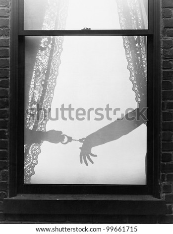 Silhouette of a hand arresting a person with handcuffs viewed through a window - stock photo