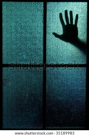 Silhouette of a hand behind a window or glass door (symbolizing horror or fear) - stock photo