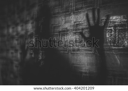 Silhouette of a hand behind the curtain