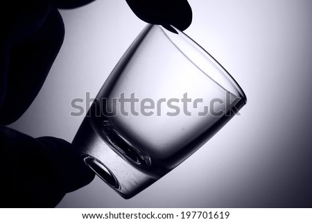 Silhouette of a hand holding an empty liquor glass. - stock photo