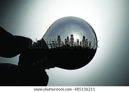 Silhouette of a hand holding an incandescent light bulb with oilfield, for the concept of global energy from fossil fuel.