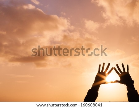 Silhouette of a hand holding up a heart at sunset. - stock photo